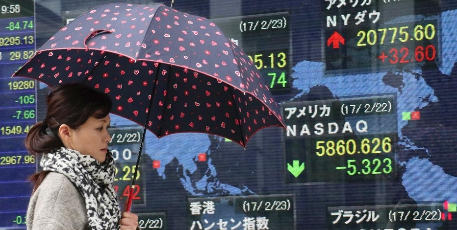 A woman walks past an electronic stock indicator of a securities firm in Tokyo, Thursday, Feb. 23, 2017. Asian shares slipped Thursday after the latest Fed minutes raised the possibility that a U.S. rate hike could come sooner than expected. (AP Photo/Shizuo Kambayashi)