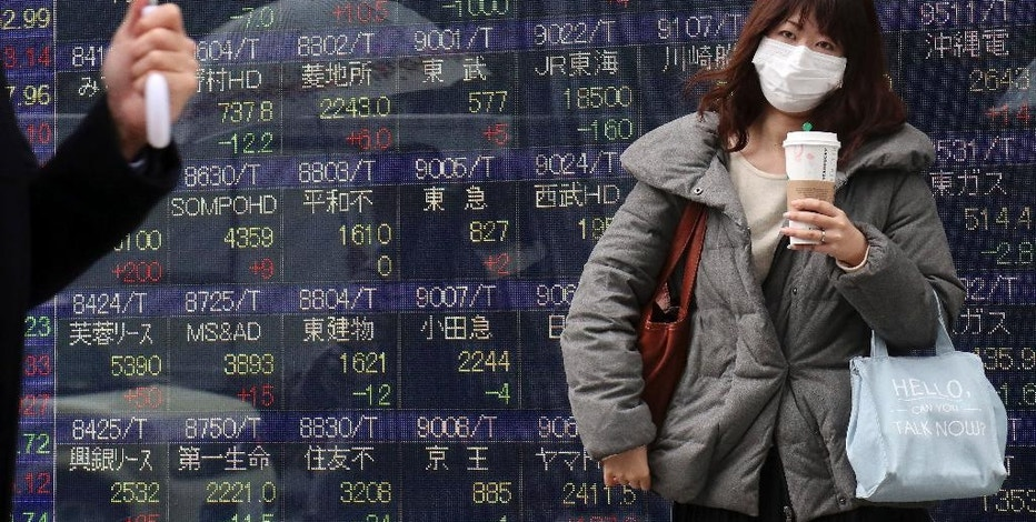 A woman waits to cross a street in front of an electronic stock indicator of a securities firm in Tokyo, Thursday, Feb. 23, 2017. Asian shares slipped Thursday after the latest Fed minutes raised the possibility that a U.S. rate hike could come sooner than expected. (AP Photo/Shizuo Kambayashi)