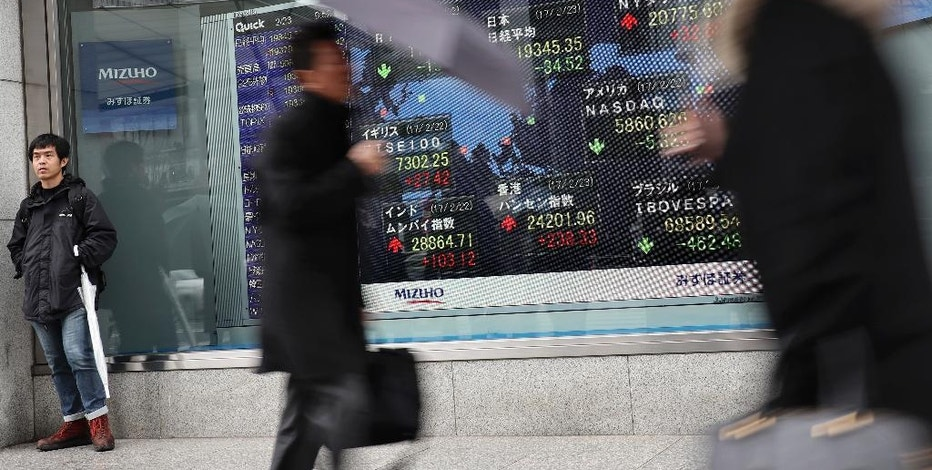 People walk past an electronic stock indicator of a securities firm in Tokyo, Thursday, Feb. 23, 2017. Asian shares slipped Thursday after the latest Fed minutes raised the possibility that a U.S. rate hike could come sooner than expected. (AP Photo/Shizuo Kambayashi)