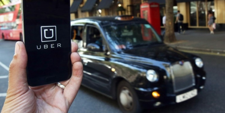 A photo illustration shows the Uber app logo displayed on a mobile telephone, as it is held up for a posed photograph in central London, Britain August 17, 2016.    REUTERS/Neil Hall/Illustration/File Photo