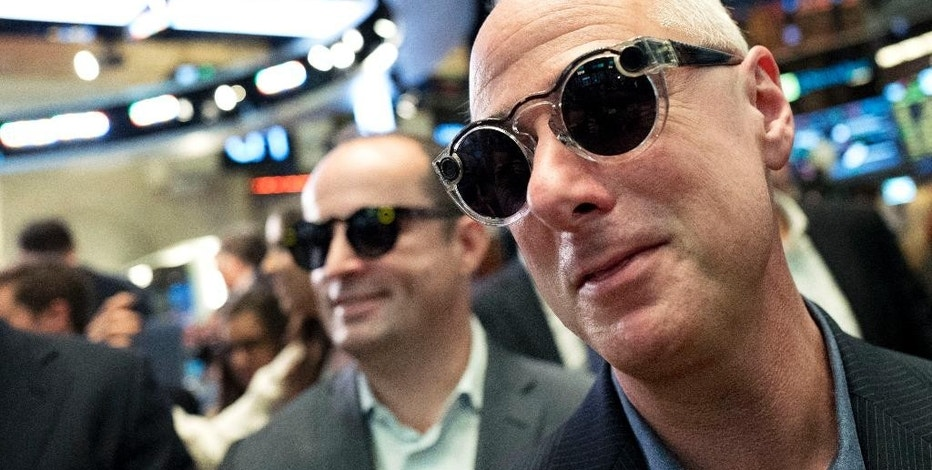 Snap employees Mark Randall, left, vice president of operations, and Steve Horowitz, vice president of engineering, wear Snap's Spectacles during the company's Wall Street debut at the New York Stock Exchange, Thursday, March 2, 2017. (AP Photo/Mark Lennihan)