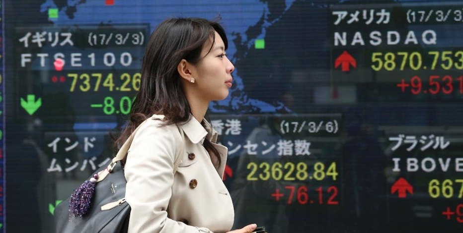 A woman walks by an electronic stock board of a securities firm in Tokyo, Monday, March 6, 2017. Shares were mixed in Asia early Monday following North Korea's launch of four ballistic missiles, three of which landed in Japan's 200-nautical mile exclusive economic zone. Hong Kong's benchmark climbed 0.3 percent after the opening of the annual session of the National People's Congress in Beijing. (AP Photo/Koji Sasahara)
