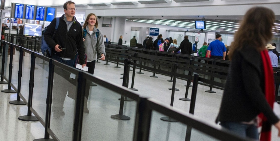 Travelers walk through a security line at John F. Kennedy International Airport in New York, November 27, 2013. A wintry blast of heavy rain, wind and snow across the eastern United States could disrupt plans on Wednesday for millions of people traveling ahead of the Thanksgiving holiday. No widespread flight cancellations were reported, but planes headed to New York's LaGuardia Airport and Philadelphia International Airport were delayed due to wind and low clouds, according to the FlightAware.com tracking site. REUTERS/Lucas Jackson (UNITED STATES - Tags: TRANSPORT SOCIETY TRAVEL) - RTX15UZ3