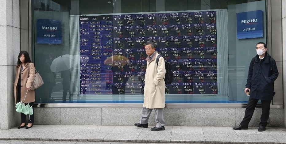 People shelter from the rain in front of an electronic stock board of a securities firm in Tokyo, Monday, March 6, 2017. Shares were mixed in Asia early Monday following North Korea's launch of four ballistic missiles, three of which landed in Japan's 200-nautical mile exclusive economic zone. Hong Kong's benchmark climbed 0.3 percent after the opening of the annual session of the National People's Congress in Beijing.(AP Photo/Koji Sasahara)