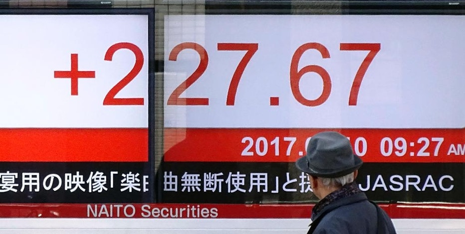 A man looks at an electronic stock board of a securities firm showing Tokyo's Nikkei 225 stock index in Tokyo, Friday, March 10, 2017. Asian stock markets were mostly higher, led by Japan, on Friday as investors awaited the U.S. employment report. South Korean stocks rose slightly after the Constitutional Court decided to remove the country's president for the first time in history. (AP Photo/Eugene Hoshiko)