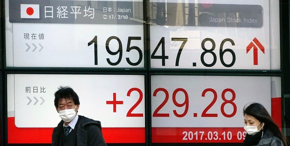 A man and a woman wearing masks walk past an electronic stock board of a securities firm showing Tokyo's Nikkei 225 stock index in Tokyo, Friday, March 10, 2017. Asian stock markets were mostly higher, led by Japan, on Friday as investors awaited the U.S. employment report. South Korean stocks rose slightly after the Constitutional Court decided to remove the country's president for the first time in history. (AP Photo/Eugene Hoshiko)