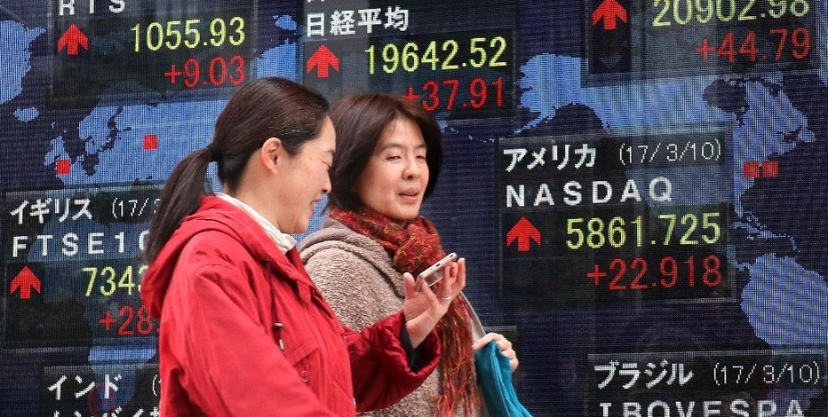 Women walk past an electronic stock indicator of a securities firm in Tokyo, Monday, March 13, 2017. Shares started the week on a high note in Asia on Monday after a strong U.S. jobs report helped drive benchmarks higher on Wall Street. A report of weakness in machinery orders in January cast a pall over trading in Tokyo. (AP Photo/Shizuo Kambayashi)