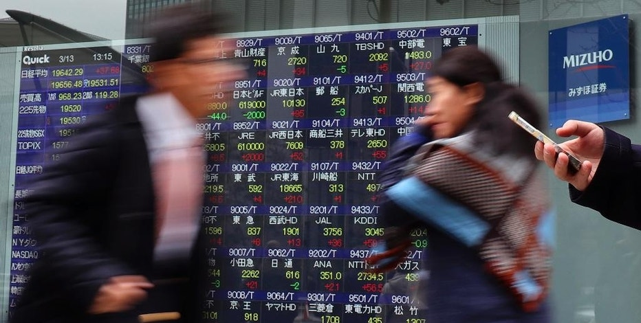 People walk past an electronic stock indicator of a securities firm in Tokyo, Monday, March 13, 2017. Shares started the week on a high note in Asia on Monday after a strong U.S. jobs report helped drive benchmarks higher on Wall Street. A report of weakness in machinery orders in January cast a pall over trading in Tokyo. (AP Photo/Shizuo Kambayashi)