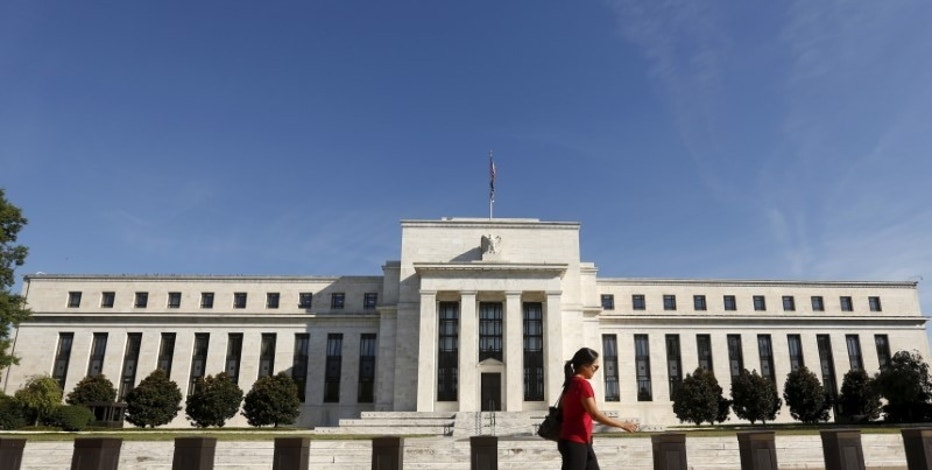A woman walks past the Federal Reserve headquarters in Washingt