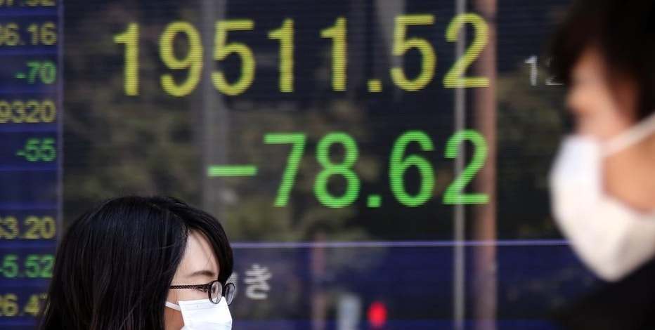 People walk by an electronic stock board of a securities firm in Tokyo, Friday, March 17, 2017. Asian markets were mixed Friday, weighing prospects that the U.S. Federal Reserve will not raise interest rates as many times as some investors expect. (AP Photo/Koji Sasahara)