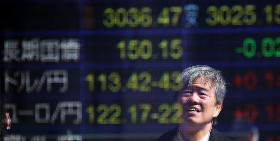 A man is reflected on the electronic board of a securities firm in Tokyo, Friday, March 17, 2017. Asian markets were mixed Friday, weighing prospects that the U.S. Federal Reserve will not raise interest rates as many times as some investors expect. (AP Photo/Koji Sasahara)
