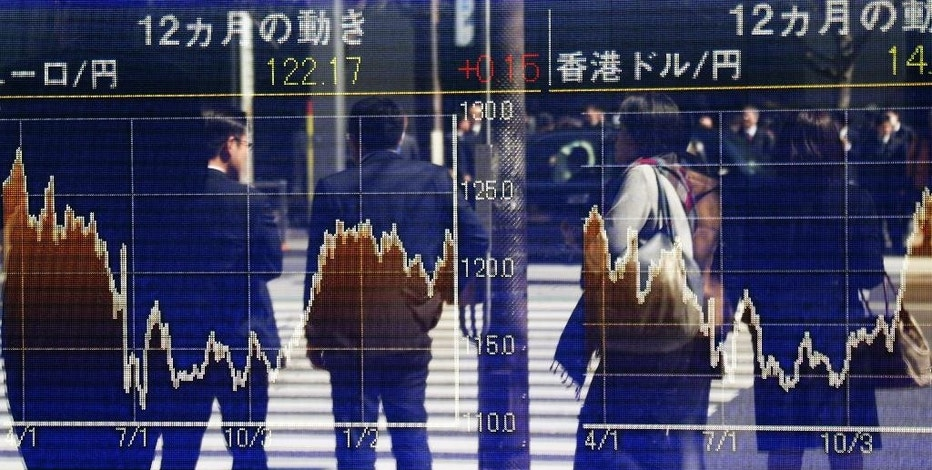 People are reflected on the electronic board of a securities firm in Tokyo, Friday, March 17, 2017. Asian markets were mixed Friday, weighing prospects that the U.S. Federal Reserve will not raise interest rates as many times as some investors expect. (AP Photo/Koji Sasahara)