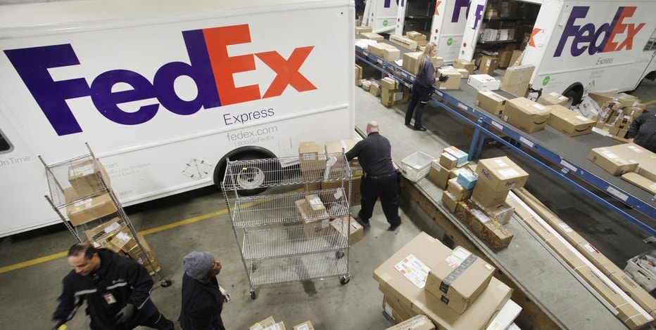 In this Dec. 15, 2014, file photo, employees pull boxes from a conveyor belt and fill their trucks for deliveries at a FedEx sorting facility in the Bronx borough of New York.