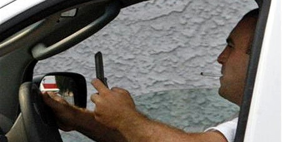 A man uses a cell phone while driving in Burbank, California June 25, 2008.