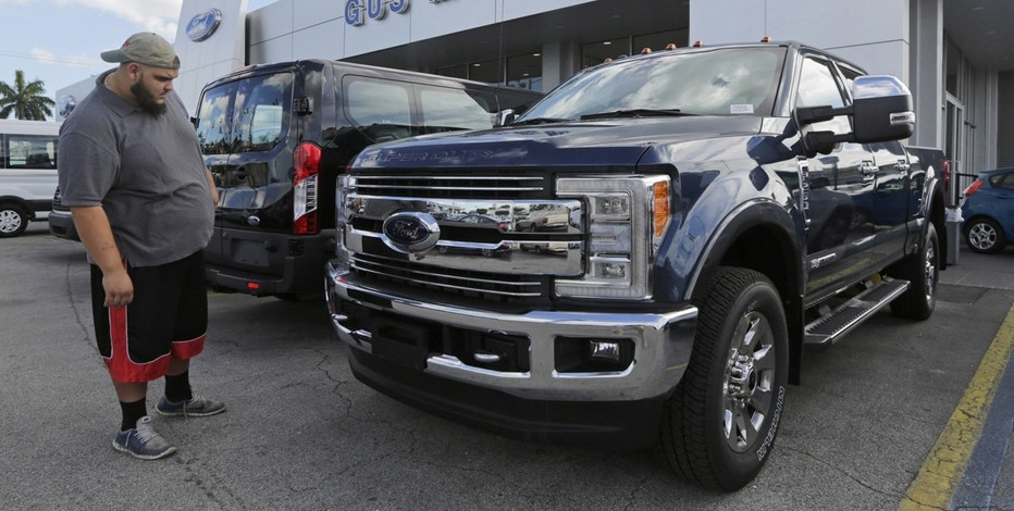 In this Tuesday, Jan. 17, 2017, photo, a potential customer looks at a 2017 Ford F-250 Lariat FX4 at a Ford dealership, in Hialeah, Fla. Ford Motor Company reports financial results Thursday, Jan. 26, 2017.