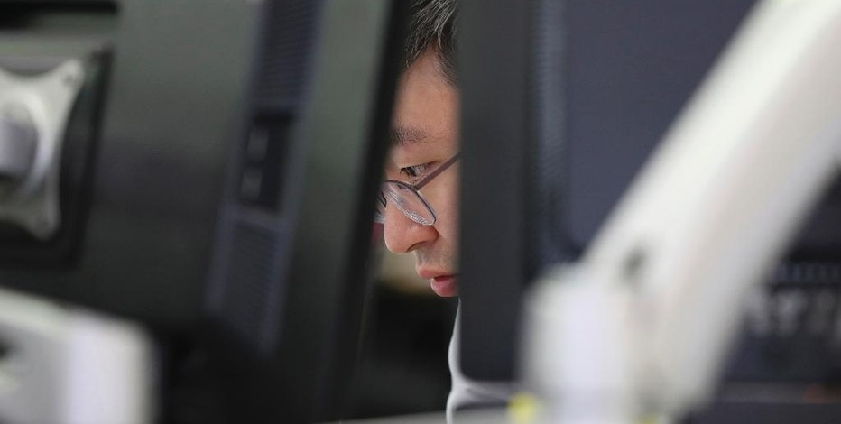 A currency trader watches monitors at the foreign exchange dealing room in Seoul, South Korea, Tuesday, April 4, 2017. Asian stock markets were mostly lower on Tuesday after disappointing U.S. car sales data contributed to a bleak day on Wall Street. Investors are cautiously awaiting President Donald Trump's meeting with the Chinese president later this week. (AP Photo/Lee Jin-man)