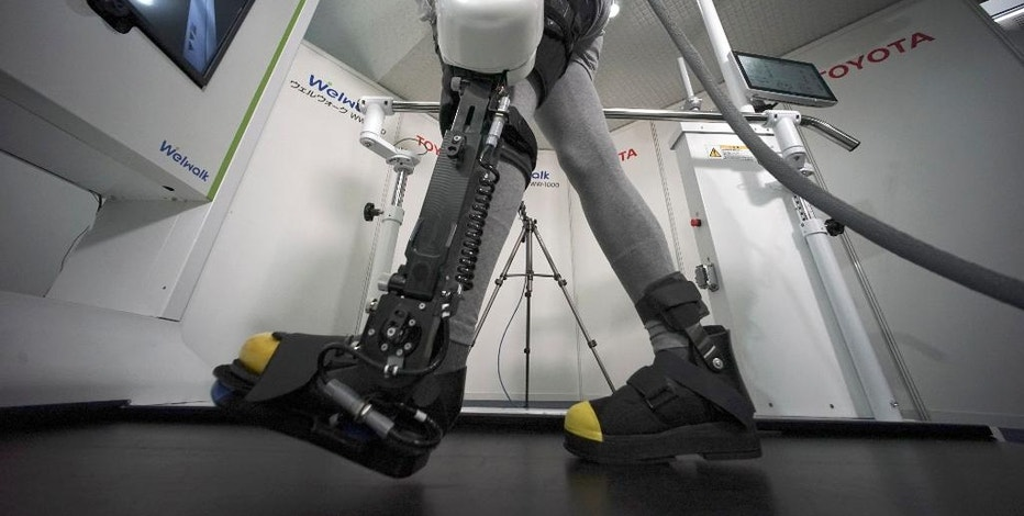 A model demonstrates the Welwalk WW-1000, a wearable robotic leg brace designed to help partially paralyzed people walk at the main system with treadmill and monitor,  at Toyota Motor Corp.'s head office in Tokyo, Wednesday, April 12, 2017. Toyota Motor Corp.'s Welwalk WW-1000 system is made up of a motorized mechanical frame that fits on a person's leg from the knee down. (AP Photo/Eugene Hoshiko)