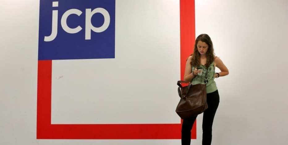 A woman checks her phone outside the entrance of a J.C. Penney store in New York August 14, 2013.   REUTERS/Brendan McDermid/File Photo