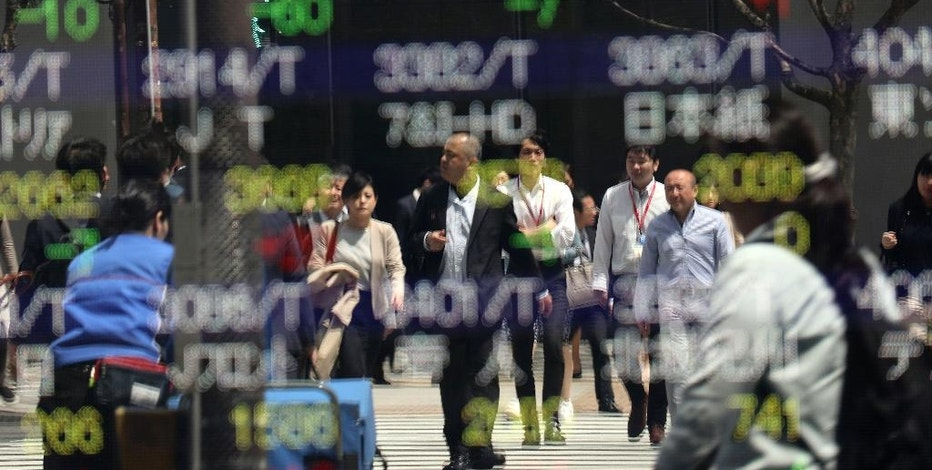 People wait to cross a street in front of an electronic stock indicator of a securities firm in Tokyo, Thursday, April 20, 2017. Shares were mostly higher in Asia on Thursday after crude oil prices rebounded from an overnight sell-off and Japan reported stronger-than-expected exports in March. (AP Photo/Shizuo Kambayashi)
