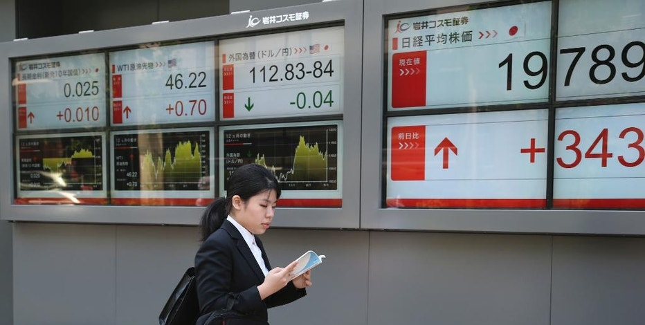 A woman walks by an electronic stock board of a securities firm in Tokyo, Monday, May 8, 2017. Asian shares rose Monday after Emmanuel Macron, a centrist would-be reformer and supporter of the European Union, won the French presidential election. (AP Photo/Koji Sasahara)