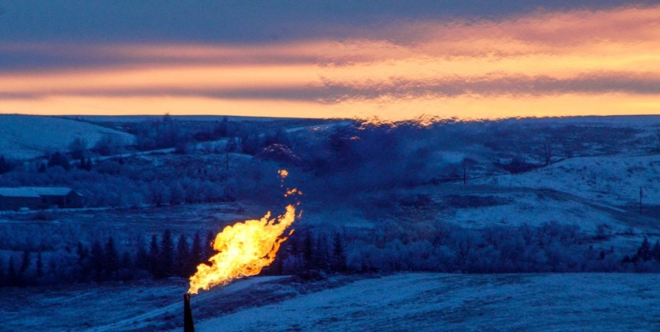 A natural gas flare on an oil well pad burns as the sun sets outside Watford City, North Dakota January 21, 2016. Persistent low oil prices have lead to slower business in much of North Dakota's Bakken oil fields.