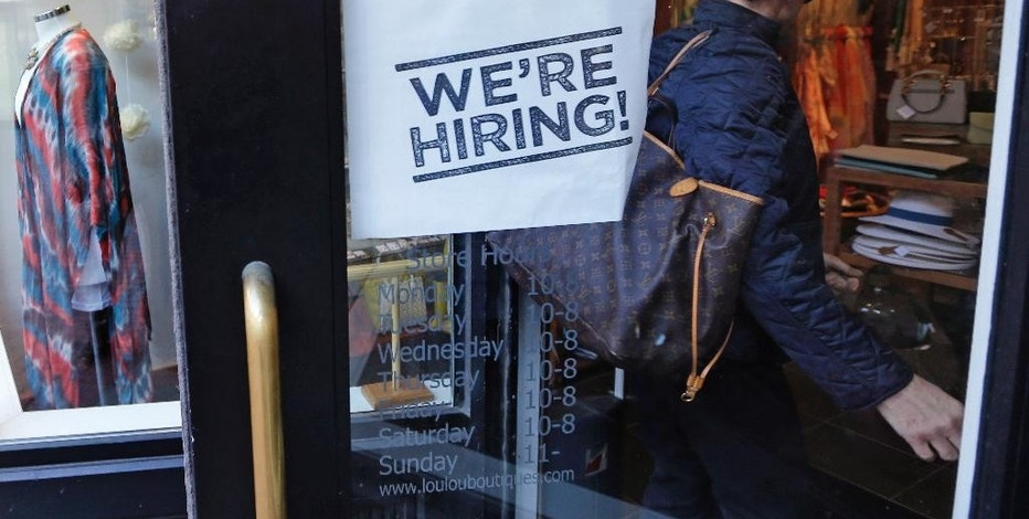 "FILE - In this Wednesday, May 18, 2016, file photo, a woman passes a ""We're Hiring!"" sign while entering a clothing store in the Downtown Crossing of Boston. On Tuesday, May 9, 2017, the Labor Department reports on job openings and labor turnover for March. (AP Photo/Charles Krupa, File)"