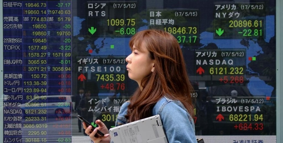 "A woman walks by an electronic stock board of a securities firm in Tokyo, Monday, May 15, 2017. Shares were higher in early trading Monday in Asia, despite worries of disruptions from the ""WannaCry"" ransomware cyberattack over the weekend. Yet another missile launch by North Korea also appeared to have little impact, while upbeat talk on trade and infrastructure investment at a top-level conference in China brightened sentiment. (AP Photo/Koji Sasahara)"