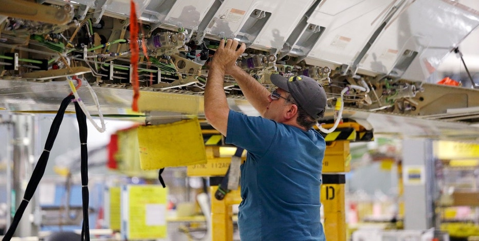 A worker assembles a Boeing's 737 MAX airplane wing at the company's production facility Monday, Feb. 13, 2017, in Renton, Wash. Boeing plans to deliver its first 737 MAX airplane by May. Boeing's latest innovations inside its Renton factory includes new robotic machines as well as more efficient ways of deploying its mechanics. The company is also increasing its 737 production rate to 47 per month, from 42. (AP Photo/Elaine Thompson)