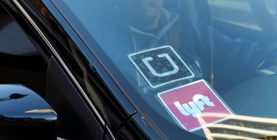 FILE - In this Tuesday, Jan. 12, 2016, file photo, a driver displaying Lyft and Uber stickers on his front windshield drops off a customer in downtown Los Angeles. Hailing a ride with a smartphone app in many U.S. cities could come down to a fight over fingerprints. Following incidents where Uber drivers were found to have criminal records, a growing number of state and local governments want ride-hailing drivers to undergo fingerprint background checks. Uber and its chief rival, Lyft, have fought those checks, contending their own method of vetting drivers is just as safe. (AP Photo/Richard Vogel, File)