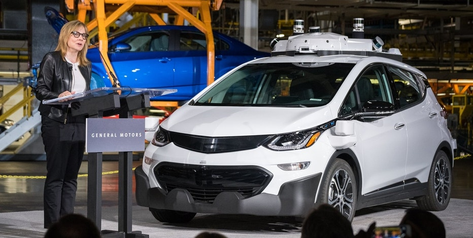 GM CEO Mary Barra speaks to employees with a self-driving Chevrolet Bolt electric vehicle on stage.