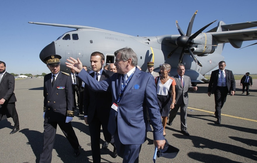 French President Emmanuel Macron, center left, listens to Emeric d'Arcimoles, center right, after exiting an Airbus A400M turboprop transport plane as part of the Paris Air Show in Le Bourget, north of Paris, Monday, June 19, 2017. Macron landed Monday at the Bourget airfield in an Airbus A400-M military transport plane to launch the aviation showcase, where the latest Boeing and Airbus passenger jets will vie for attention with a F-35 warplane, drones and other and high-tech hardware.
