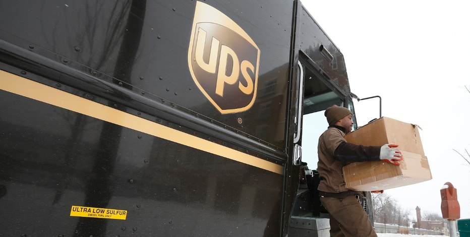 A UPS driver steps off his truck to deliver packages in Evanston, Illinois, March 5, 2014. United Parcel Service Inc, the world's largest courier company, said it would buy 1,000 propane-fueled delivery trucks and install 50 fueling stations in the United States as it expands its already-large fleet of alternative-fuel vehicles. REUTERS/Jim Young (UNITED STATES - Tags: BUSINESS ENERGY TRANSPORT) - RTR3G2TD
