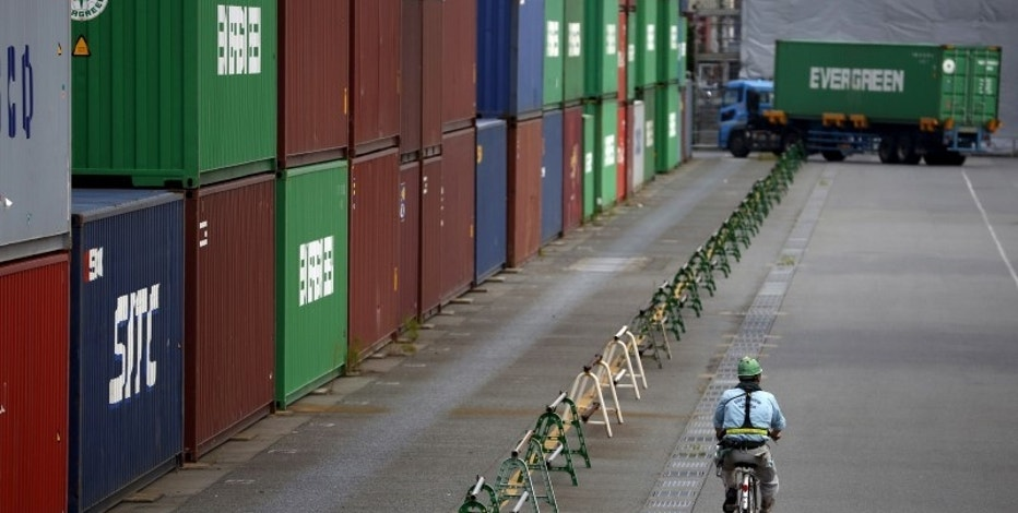 A worker rides a bicycle past containers at a port in Tokyo August 19, 2015.   REUTERS/Issei Kato/File Photo