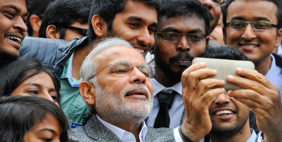 Indian Prime Minister Narendra Modi poses for selfies with Indian students during a visit at the French National Space Agency (CNES) in Toulouse April 11, 2015.