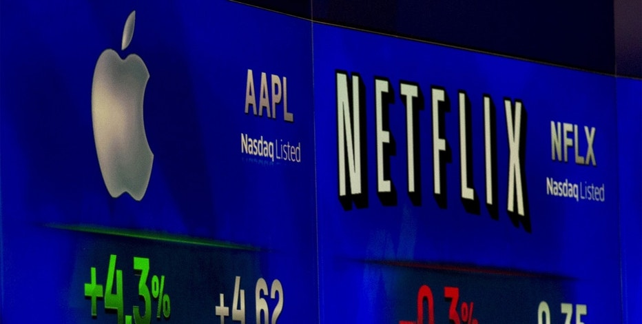 A reporter points at ticker symbols for Apple Inc. and Netflix displayed on a screen at the Nasdaq Market site in New York September 2, 2015.