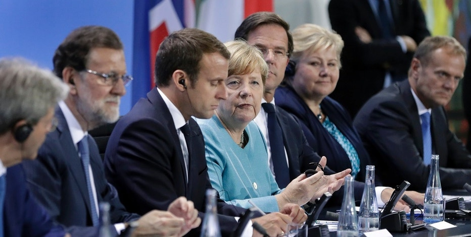 From left, Italian Prime Minister Paolo Gentiloni, Spain's Prime Minister Mariano Rajoy, France's President Emmanuel Macron, German Chancellor Angela Merkel, the Netherland's Prime Minister Mark Rutte, Norway's Prime Minister Erna Solberg and European Council President Donald Tusk, address the media during a joint press conference after a pre-G20 meeting at the chancellery in Berlin, Germany, Thursday, June 29, 2017. (AP Photo/Michael Sohn)