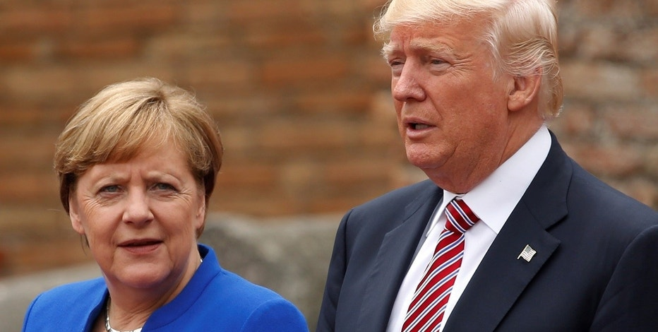 U.S. President Donald Trump and German Chancellor Angela Merkel pose during a family phto at the Greek Theatre during a G7 summit in Taormina, Sicily, Italy, May 26, 2017. REUTERS/Jonathan Ernst - RTX37RGG