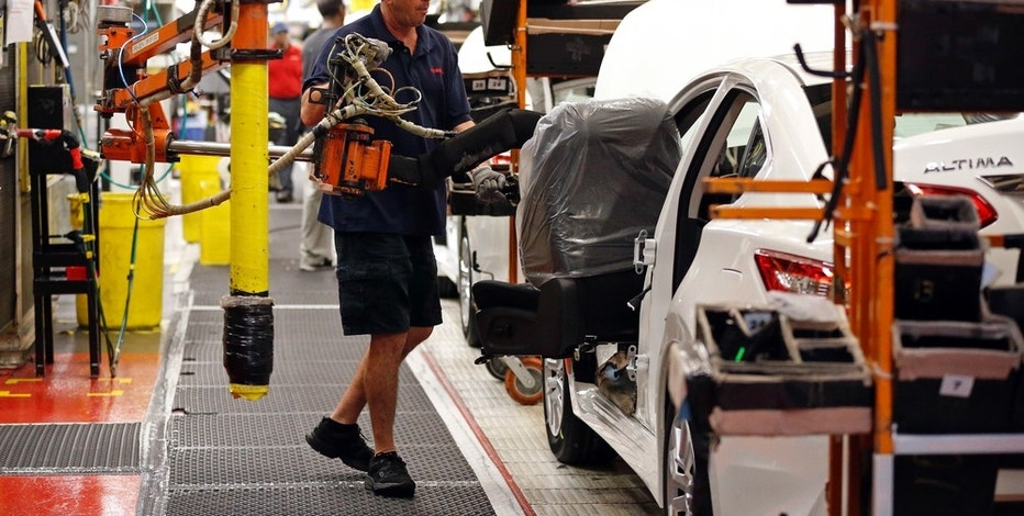 In this April 6, 2016, photograph, Nissan technician David Newton uses a lift to move a front seat for installation into a new Altima on the assembly line at the Nissan Canton Vehicle Assembly Plant in Canton, Miss. U.S. businesses ramped up their investment in industrial machinery, semiconductors, and other big-ticket items in December 2016, boosting demand for factory goods. Auto sales reached a record level in 2016, and automakers continued cranking out vehicles through the end of the year. (AP Photo/Rogelio V. Solis)