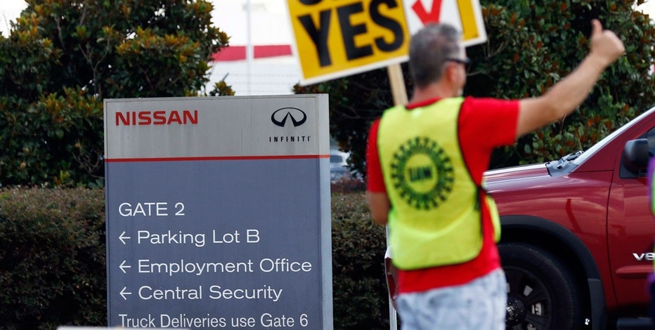 A United Auto Workers sign-bearing member stands outside an employee vehicle entrance at the Nissan vehicle assembly plant in Canton, Miss., and greets each arriving vehicle, Thursday, Aug. 3, 2017.