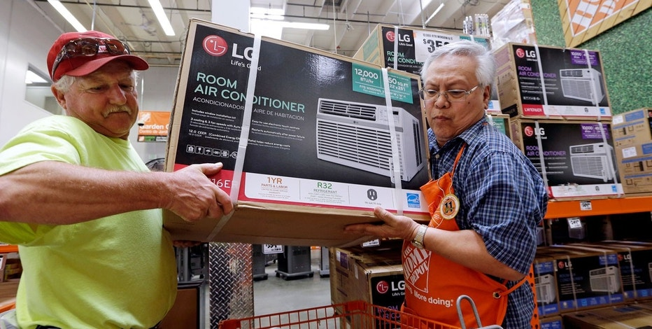 In this Tuesday, Aug. 1, 2017, file photo, store greeter Danny Olivar, right, lends a hand to a customer, who declined to be identified, to heft an air conditioning unit from a rapidly declining stock at a Home Depot store ahead of an expected heat wave in Seattle.