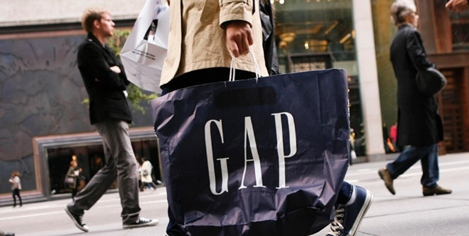 A shopper walks down Fifth Avenue carrying a Gap shopping bag in New York October 8, 2009. U.S. retailers posted their first monthly sales increase in more than a year. REUTERS/Lucas Jackson (UNITED STATES BUSINESS) - RTXPG3E