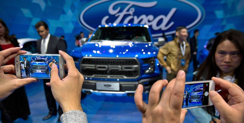 In this April 23, 2016, photo, attendees take smartphone photos at a promotional event for Ford Motor Company ahead of the Auto China car show in Beijing.
