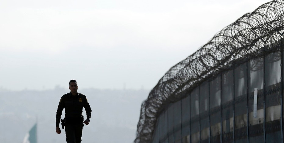 FILE - In this June 22, 2016 file photo, Border Patrol agent Eduardo Olmos walks near the secondary fence separating Tijuana, Mexico, background, and San Diego in San Diego. The Trump administration said Tuesday, Aug. 1, 2017, that it will waive environmental reviews and other laws to replace a stretch of border wall in San Diego, moving to make good on one of the president's signature campaign pledges. (AP Photo/Gregory Bull, File)