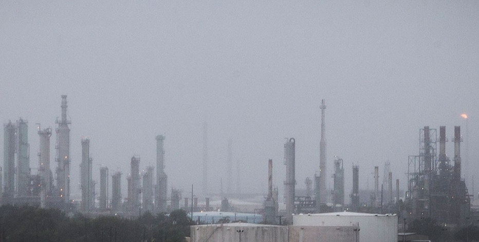 An oil refinery flare, right, continues to burn through wind and rain as Hurricane Harvey moves into Corpus Christi, Texas, on Friday, Aug. 25, 2017. Hurricane Harvey is expected to make landfall on the Texas coast Friday night or early Saturday morning.