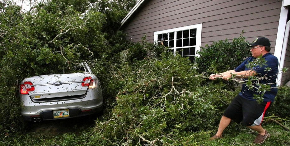 Resident Tim Harper clears brush to get to his car in the Dommerich Estates neighborhood in Maitland Fla., Monday, Sept. 11, 2017, after Hurricane Irma's passing through central Florida.