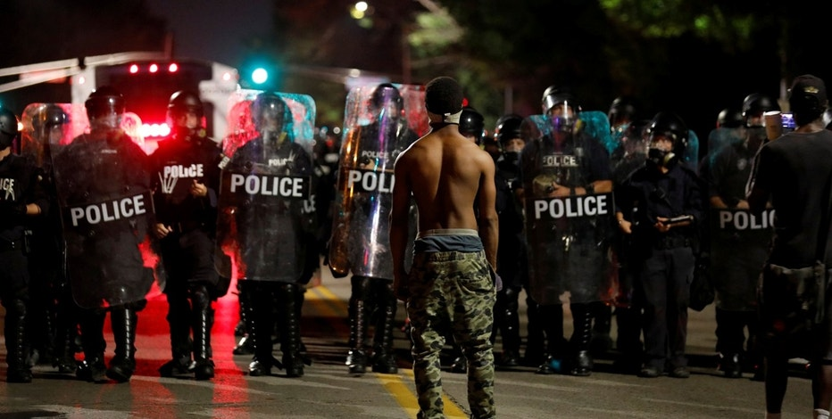 A protester faces off with law enforcement officials after Jason Stockley, a former St. Louis police officer, was acquitted of murder in the 2011 fatal shooting of Anthony Lamar Smith, a black man suspected of dealing drugs, in St. Louis, Missouri, U.S. September 15, 2017. REUTERS/Whitney Curtis