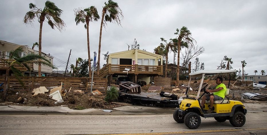 A man drives by debris cluttered properties in Port Aransas, Texas, Sunday, Aug. 27, 2017. Harvey made landfall in Texas on Friday night as the strongest hurricane to hit the U.S. in more than a decade. By Saturday afternoon it had been downgraded into a tropical storm, but it had dumped over a dozen inches of rain on some areas and forecasters were warning that it could cause catastrophic flooding in the coming days.