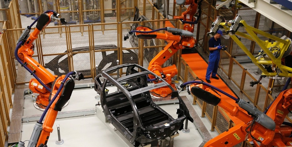 A worker makes technical measurements with robots on the carbon chassis at the serial production BMW i3 electric car in the BMW factory in Leipzig September 18, 2013.  REUTERS/Fabrizio Bensch (GERMANY - Tags: TRANSPORT) - RTX13PUL
