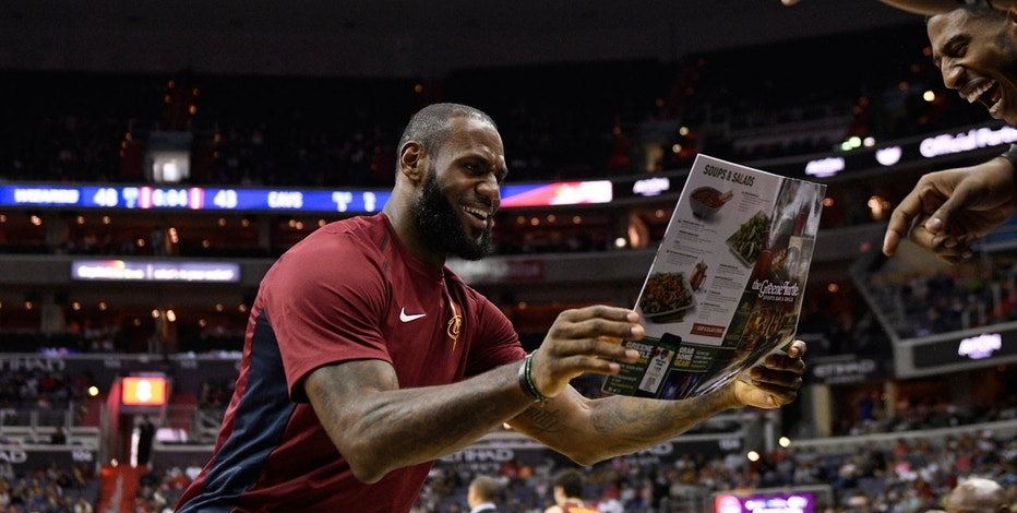 Cleveland Cavaliers forward LeBron James reacts and looks at a menu after a dunk by teammate Jeff Green during the first half of an preseason NBA basketball game against the Washington Wizards, Sunday, Oct. 8, 2017, in Washington.