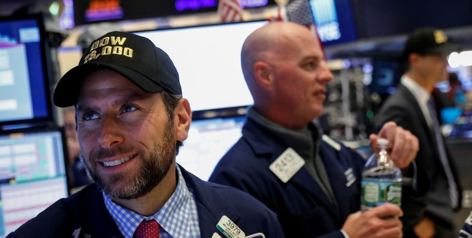 Specialist trader Michael Pistillo Jr. wears a Dow 23,000 hat, after the Dow briefly traded above 23,000, at his post on the floor of the New York Stock Exchange (NYSE) in New York, U.S., October 17, 2017.